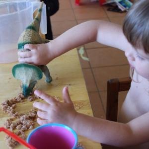 Ester konzumuje jídlo pomocí dinosaura.