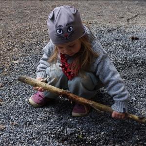 Ester hledá poklad v hromadě štěrku.